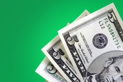Five dollar bills against green background.